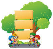 Wooden sign template with kids on bike Stock Image
