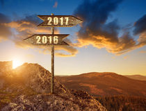 Wooden sign with text 2016 and 2017 at sunset. Stock Photos