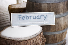 Wooden sign on tree stump with the word February. Blue wooden sign on tree stump with the word February written on it Royalty Free Stock Photos