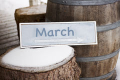 Wooden sign on tree stump with the word March stock image