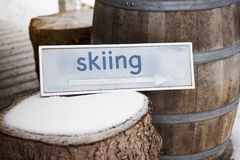 Wooden sign on tree stump with the word Skiing royalty free stock image