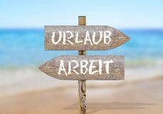Wooden sign words Arbeit and Urlaub, translation: Work and Vacat Stock Photos