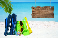 Wooden signboard on the beach. Wooden signboard with copy space, flip flops, sunnglasses and beach toys on the sunny beach royalty free stock photo