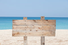 Wooden signboard on blue sky and on tropical beach for summer ba Stock Image