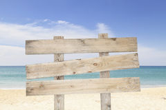 Wooden signboard on blue sky and on tropical beach for summer ba Stock Photo