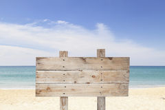 Wooden signboard on blue sky and on tropical beach for summer ba Royalty Free Stock Photo