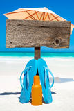 Wooden signboard with copy space. And flip flops with a bottle suntan lotion on the sunny beach with a sunshades in the background Royalty Free Stock Image