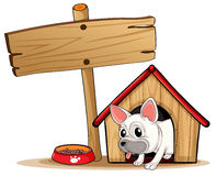 A wooden signboard beside a doghouse Stock Photography