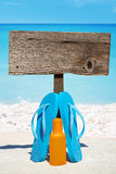 Wooden signboard and flip flops on beach. Wooden signboard with copy space and flip flops with a bottle suntan lotion on the sunny beach Stock Photo