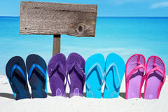 Wooden signboard and flip flops. Wooden signboard with copy space behind a row of colorful flip flops on the sunny beach Royalty Free Stock Images