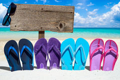 Wooden signboard and flip flops. Wooden signboard with copy space, sunglasses and a row of colorful flip flops on the sunny beach Stock Images