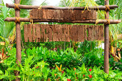 Wooden signboard among green plantation.  Royalty Free Stock Images