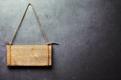 Wooden signboard hanging on rope on gray textured wall Royalty Free Stock Photo