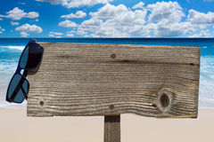 Wooden signboard on sunny beach Stock Image