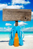 Wooden signboard and suntan lotion. Wooden signboard with copy space and flip flops with a bottle suntan lotion on the sunny beach Stock Image