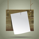 Wooden signboard suspended on a rope with a white paper sheet. Stock Image
