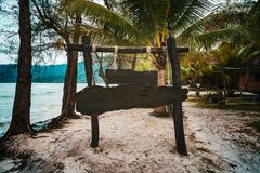 Wooden signboard on tropical beach. A sign board for the name of the hotel or the beach on a background of beautiful nature on. A tropical island stock photography