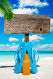 Wooden signboard under palm frond. Wooden signboard with copy space and blue flip flops under palm fronds on the summer beach Royalty Free Stock Photography