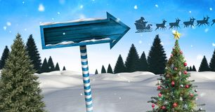 Wooden signpost in Christmas Winter landscape with Christmas tree and Santa`s sleigh and reindeers. Digital composite of Wooden signpost in Christmas Winter Royalty Free Stock Image