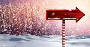 Wooden signpost in Christmas Winter landscape. Digital composite of Wooden signpost in Christmas Winter landscape Royalty Free Stock Photos