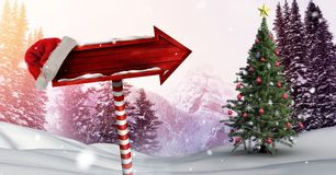 Wooden signpost in Christmas Winter landscape and Santa hat with Christmas tree. Digital composite of Wooden signpost in Christmas Winter landscape and Santa hat Royalty Free Stock Photos