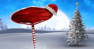 Wooden signpost in Christmas Winter landscape and Santa hat with Christmas tree. Digital composite of Wooden signpost in Christmas Winter landscape and Santa hat Stock Photography