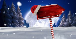 Wooden signpost in Christmas Winter landscape and Santa hat. Digital composite of Wooden signpost in Christmas Winter landscape and Santa hat Royalty Free Stock Photo