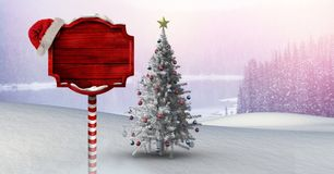 Wooden signpost in Christmas Winter landscape and Santa hat with Christmas tree. Digital composite of Wooden signpost in Christmas Winter landscape and Santa hat Stock Image
