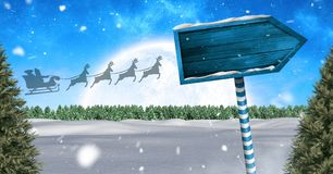 Wooden signpost in Christmas Winter landscape and Santa`s sleigh and reindeer`s. Digital composite of Wooden signpost in Christmas Winter landscape and Santa`s Royalty Free Stock Images