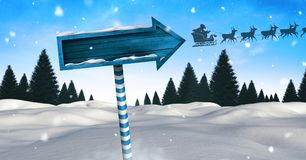 Wooden signpost in Christmas Winter landscape and Santa`s sleigh and reindeer`s. Digital composite of Wooden signpost in Christmas Winter landscape and Santa`s royalty free illustration
