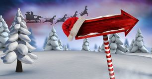 Wooden signpost in Christmas Winter landscape and Santa`s sleigh and reindeer`s. Digital composite of Wooden signpost in Christmas Winter landscape and Santa`s Royalty Free Stock Image