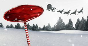 Wooden signpost in Christmas Winter landscape and Santa`s sleigh and reindeer`s. Digital composite of Wooden signpost in Christmas Winter landscape and Santa`s Stock Photos