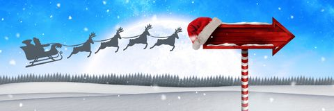 Wooden signpost in Christmas Winter landscape and Santa`s sleigh and reindeer`s. Digital composite of Wooden signpost in Christmas Winter landscape and Santa`s Royalty Free Stock Photography