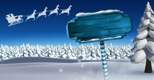 Wooden signpost in Christmas Winter landscape and Santa`s sleigh and reindeer`s. Digital composite of Wooden signpost in Christmas Winter landscape and Santa`s Royalty Free Stock Photo