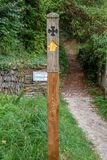 Wooden signpost with cross. Signpost for the Saints´ Way with a black cross and an yellow arrow. The Saints´ way is a footpah which runs from Padstow to stock photo