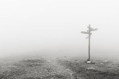 Wooden signpost in the fog Stock Photography