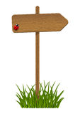 Wooden signpost with green grass Stock Photo