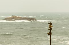 Wooden signpost with many pointers with the sea at background stock photo
