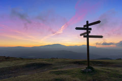 Wooden signpost on mountain. At sunset stock photos