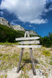 Wooden signpost on path to high mountain Stock Photo