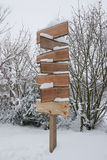 Wooden Signpost With Snow In Winter. Blank wooden signpost covered in snow on a winter day Stock Images