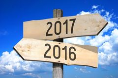 2016, 2017 - wooden signpost. Wooden signpost with two arrows `2016` and `2017` - sky with clouds in a background Stock Photos