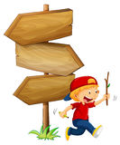 Wooden signs and little boy with stick Stock Image