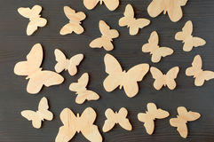 Wooden silhouettes of butterflies on a black background Stock Photos