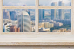 Wooden sill over blurred city view trough window Royalty Free Stock Images