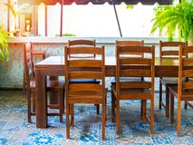 Wooden simple table and chairs on vintage tile floor stock photo