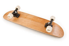 Wooden Skateboard Upside Down. A blank wooden skateboard deck turned upside down with trucks and wheels showing. Image is shot from above at an angle and is stock photography