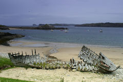 The wooden skeleton of a ship wrecked on a stony beach against a blue clouded sky with islands behind. North Scotland, Hebridies Stock Photo