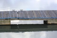 Wooden slatted walkway over water. A slatted wooden walkway over a river marina with boat tie holds and reflections in the water Royalty Free Stock Photos