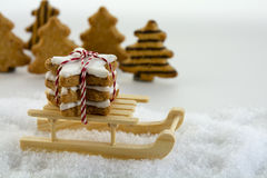 Wooden sled carries cinnamon star cookies through the snow in fr Stock Photo